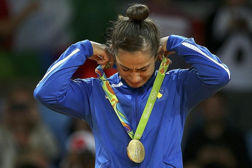 Judoka Majlinda Kelmendi is overcome by emotion after winning gold in the women's 52kg category. Hers is the first medal won at an Olympic Games by Kosovo, which has a population of only 1.8 million.