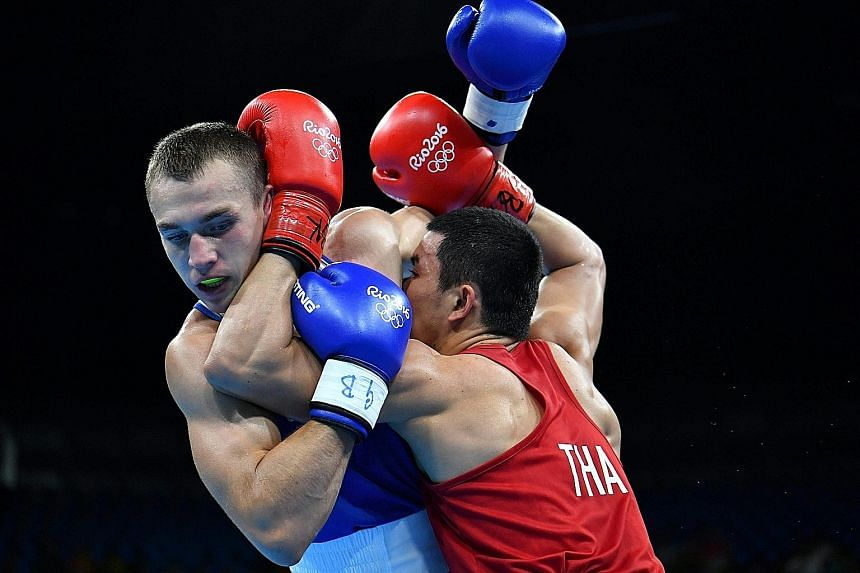 Thailand's Saylom Ardee (right) appears to use every part of his arms to fight Belarus' Pavel Kastramin during the men's welterweight round-of-32 match on Sunday. The Thai proved successful as he advanced on a split decision to the next stage.