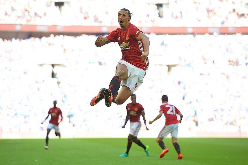 Manchester United's new signing Zlatan Ibrahimovic leaps high in celebration of his late winner in their 2-1 Community Shield victory over defending EPL champions Leicester City.