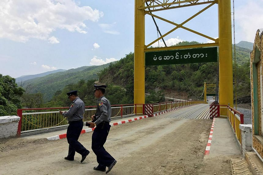 Myanmar police survey a bridge in Myanmar's Chin state, near the border with India, on May 10.