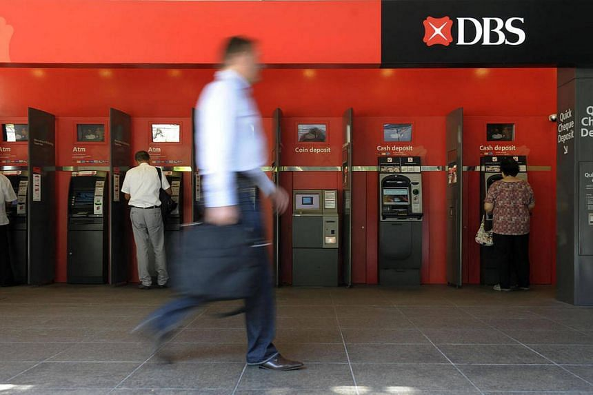 A person walks past a DBS atm at Shenton Way.