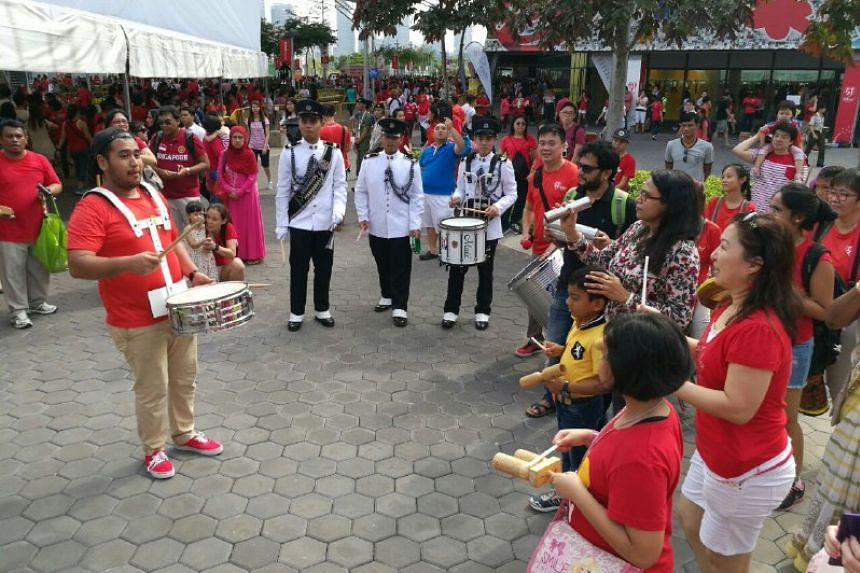 Members of the public joining in the drumming performances outside the stadium.