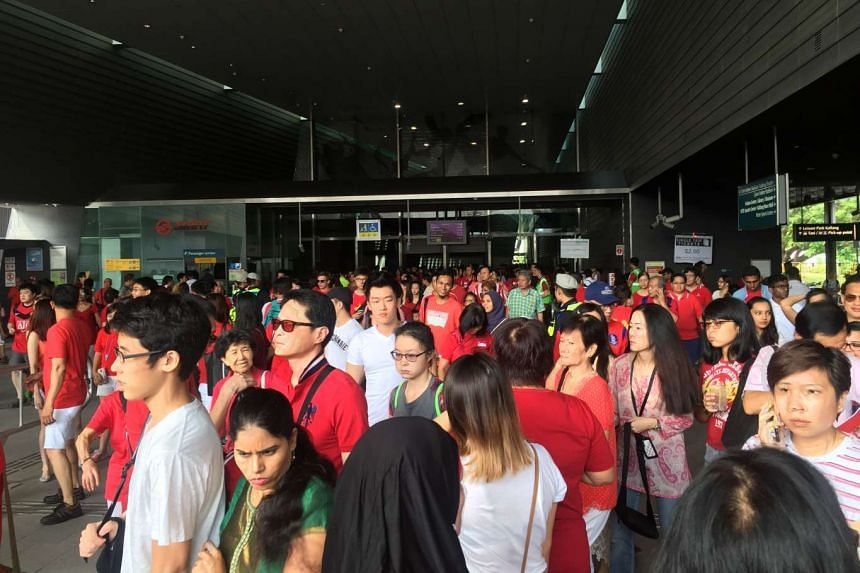 People streaming out from the entrance of Stadium MRT station.