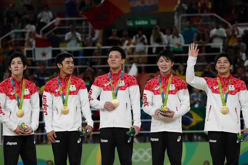 (From left) Japan's Ryohei Kato, Kenzo Shirai, Yusuke Tanaka, Kohei Uchimura and Koji Yamamuro pose with their gold medals on the podium for the Men's Team final of the Rio 2016 Olympic Games Artistic Gymnastics event.