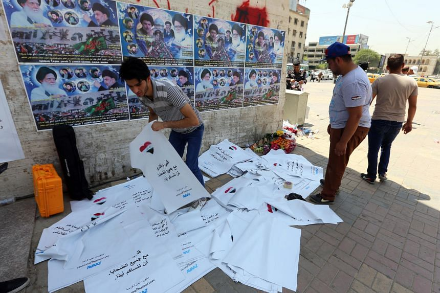 Iraqis prepare to put up posters in Baghdad's Tahrir square on August 3 bearing messages of solidarity from Nice and other cities hit by attacks.