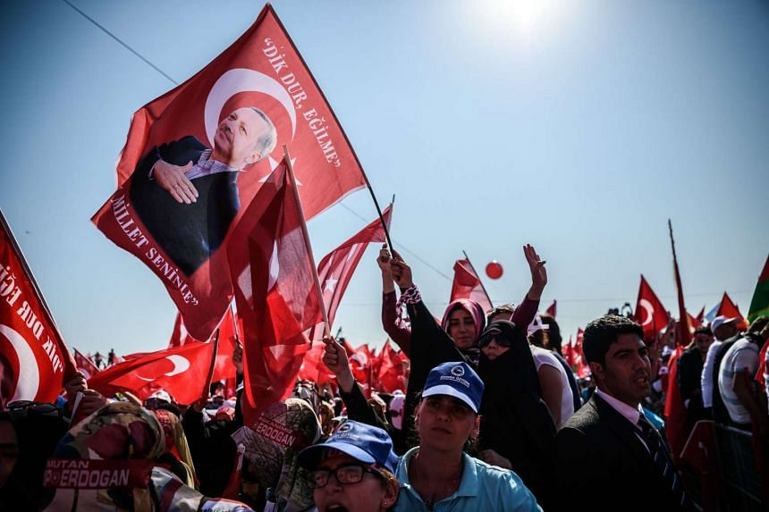 A demonstrator holds a flag picturing Turkish President Recep Tayyip Erdogan among other demonstrators on Aug 7, 2016, in Istanbul during a rally against the failed military coup.