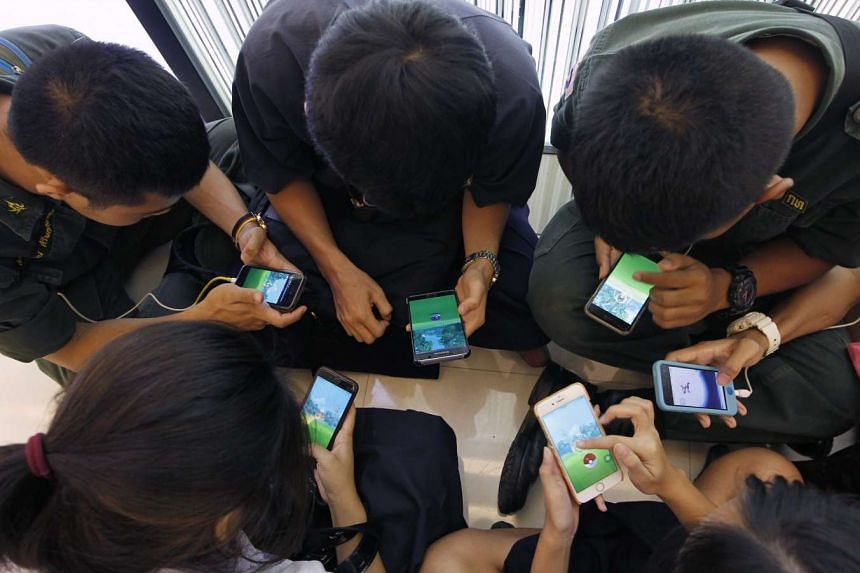 Thai students play Pokemon Go on their smartphones at a shopping mall in Bangkok, on Aug 8, 2016.