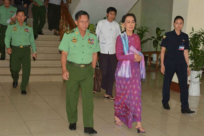Myanmar State Counsellor and Foreign Minister Aung San Suu Kyi (right) and military chief Senior General Min Aung Hlaing (left) walk to a meeting in Naypyidaw on Aug 8, 2016.