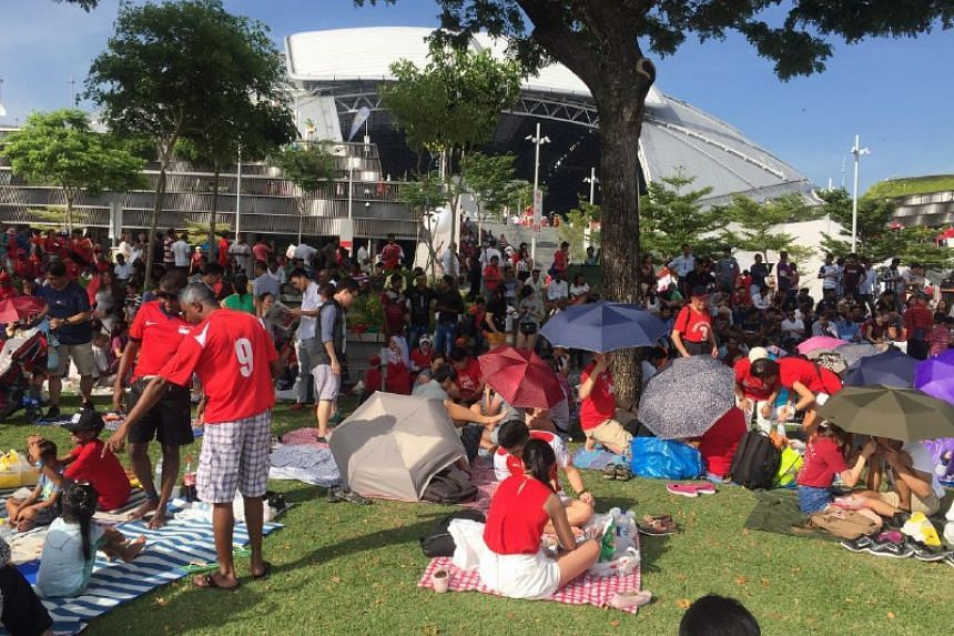 People have a picnic outside the National Stadium.