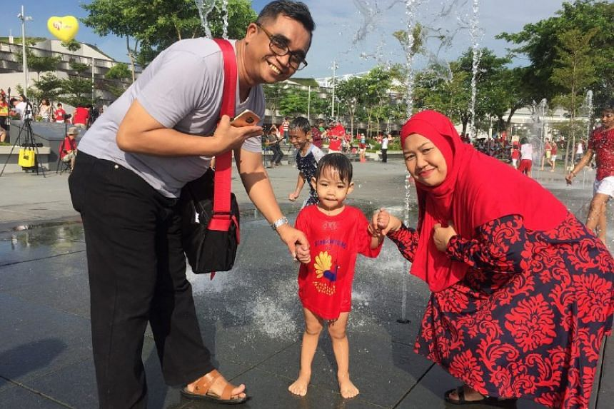 A family poses for a picture near a water fountain outside the National Stadium.