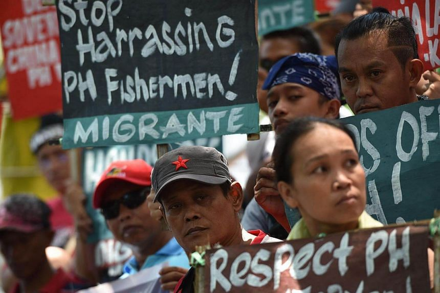 Activists hold anti-China placards during a protest in front of the Chinese consulate in Manila on July 12, 2016, ahead of UN tribunal ruling regarding the South China Sea.