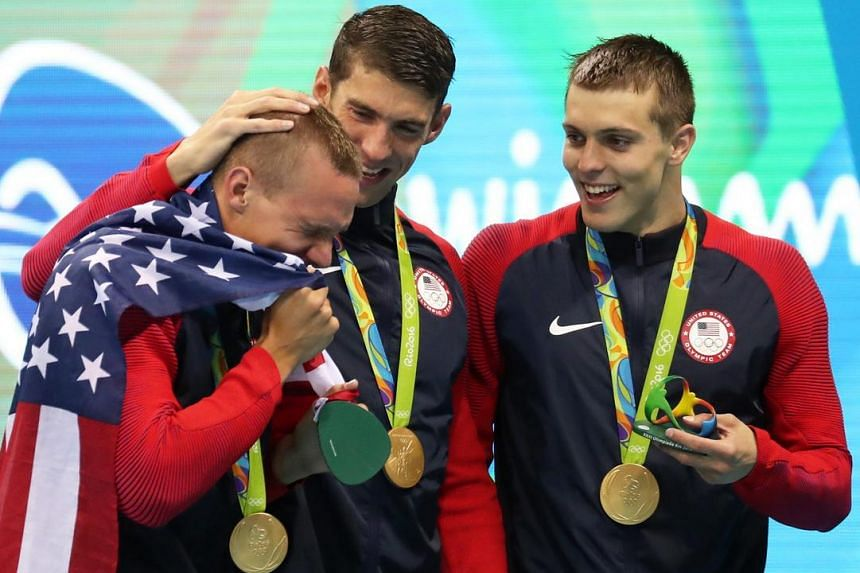 US' gold medalist Caeleb Dressel (left) reacts next to teammates Michael Phelps (centre) and Ryan Held (right) during the medal ceremony for the men's 4x100m Freestyle relay final race of the Rio 2016 Olympic Games Swimming events on August 7.