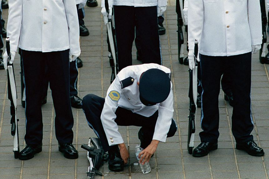 A soldier giving his boots a last-minute buff as the air force guard-of-honour contingent forms outside the National Stadium at the 1998 preview show.