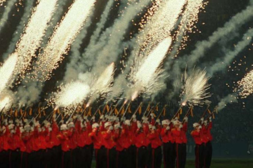 Certified crowd-pleasers, the SAF Provost Unit Precision Drill Squad dazzle the crowd at the 1998 preview show with their nifty footwork and whistling fireworks.