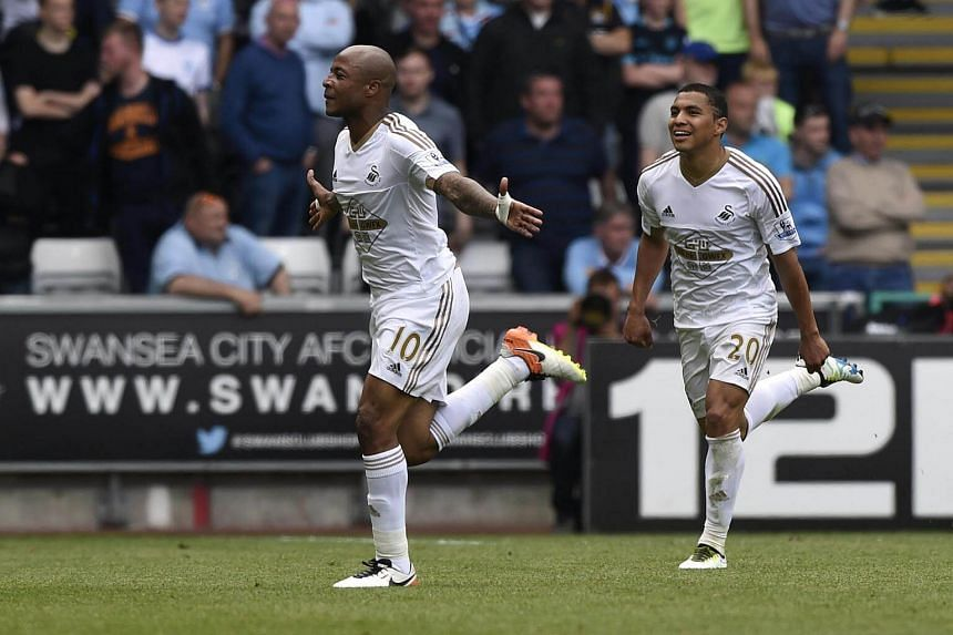 Andre Ayew (left) celebrates after scoring the first goal for Swansea against Manchester City.