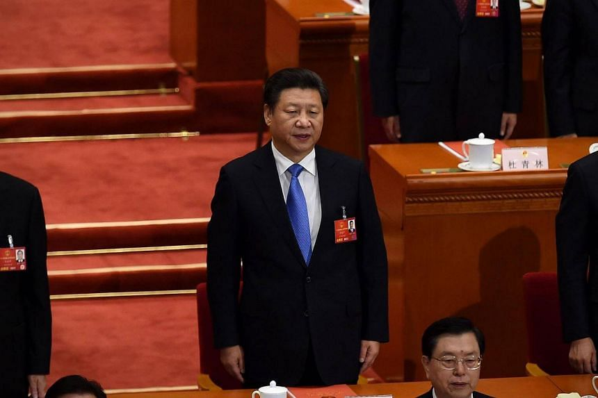Chinese President Xi Jinping seen singing the national anthem during the closing session of the National People's Congress in Beijing on March 16.