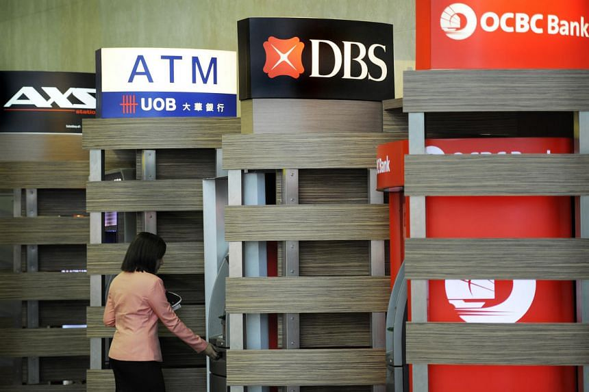 A customer uses a DBS Group Holdings Ltd. automated teller machine (ATM), standing between the ATMs of United Overseas Bank Ltd. and Oversea-Chinese Banking Corp. Ltd., at Changi Airport in Singapore.