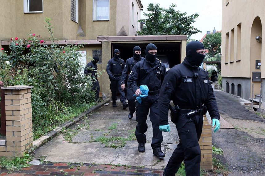 Masked police forces leave after searching a house in Hildesheim, Germany on Aug 10, 2016.