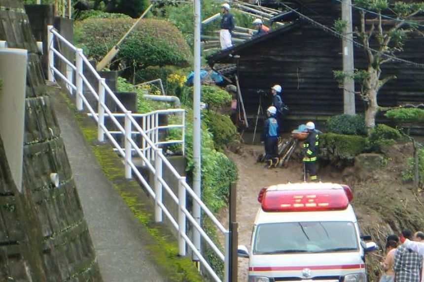 Local firefighters inspect the area following a landslide in the southern Japanese city of Kumamoto on June 21, 2016.