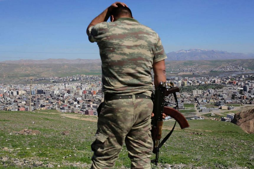 A Turkish soldier standing on the hill overlooking damaged buildings in south-eastern Turkey.