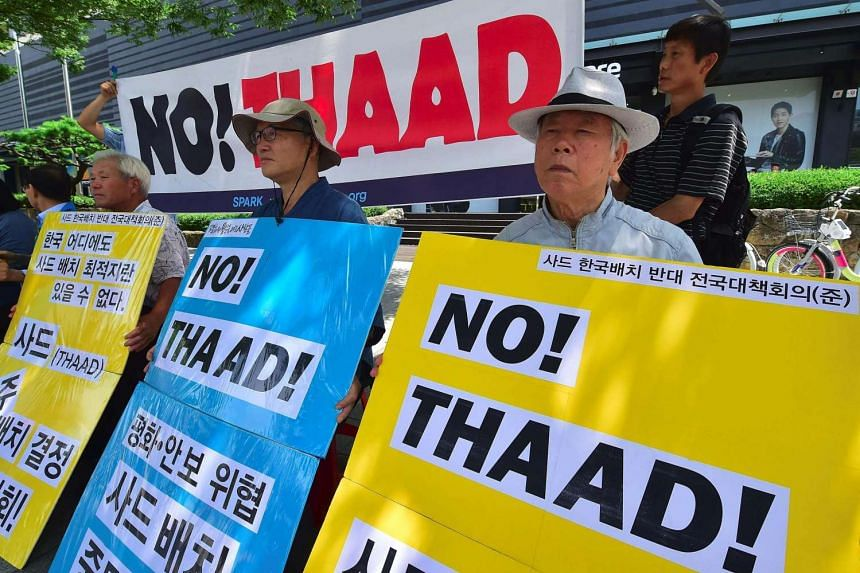 South Korean activists hold placards during a protest against the planned deployment of the US-built Terminal High Altitude Area Defense, THAAD, near the US embassy in Seoul on July 19.