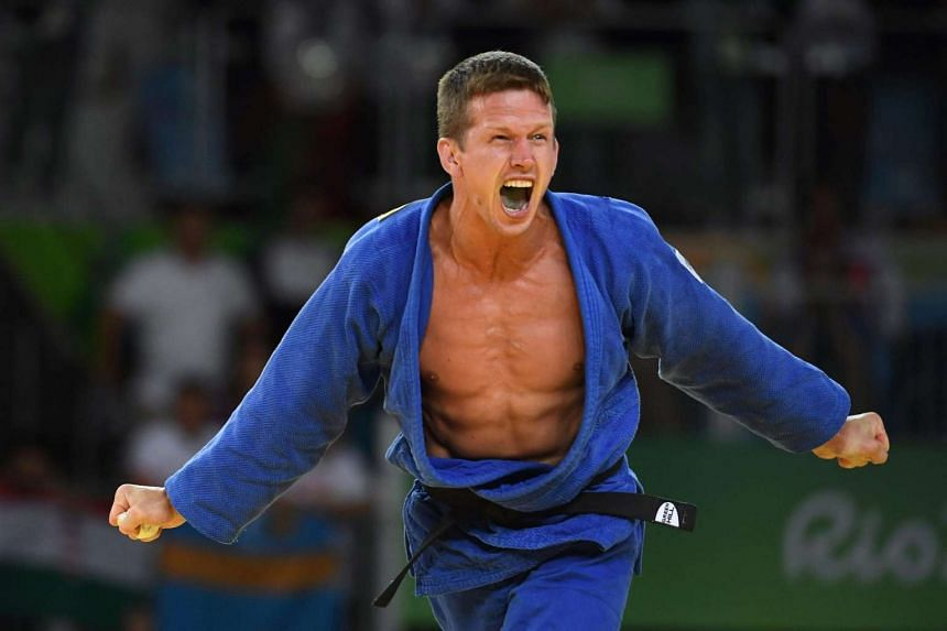 Belgium's Dirk van Tichelt celebrates after defeating Hungary's Miklos Ungvari in their men's under-73kg judo bronze medal B match at the Rio 2016 Olympic Games on Aug 8.