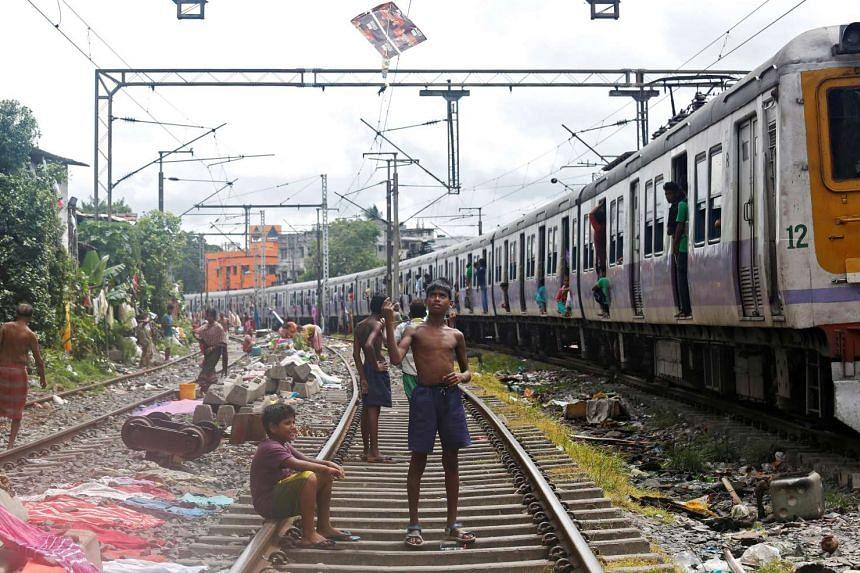A boy flies a kite on a railway track as a train passes through in Kolkata, India.