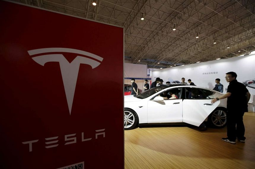People looking at a Tesla Model S during the Auto China 2016 show in Beijing on April 25, 2016.
