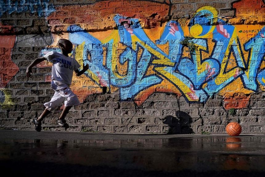 A young migrant runs after a ball in the street of Via Cupa, outside the former Baobab migrants reception centre next to the Tiburtina train station in Rome on Monday. Set up almost three years ago, the Baobab centre was shut down by police in Decemb