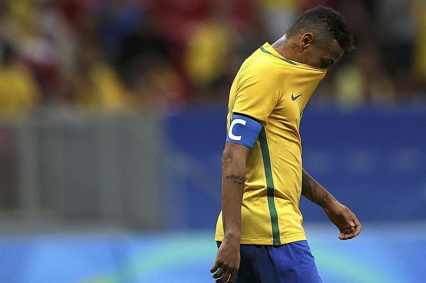 Left: Neymar walking off the pitch after Brazil's 0-0 draw with Iraq, leaving the hosts needing victory in their final group game against Denmark today. The Selecao had already suffered one disappointment this year with their early Copa America exit