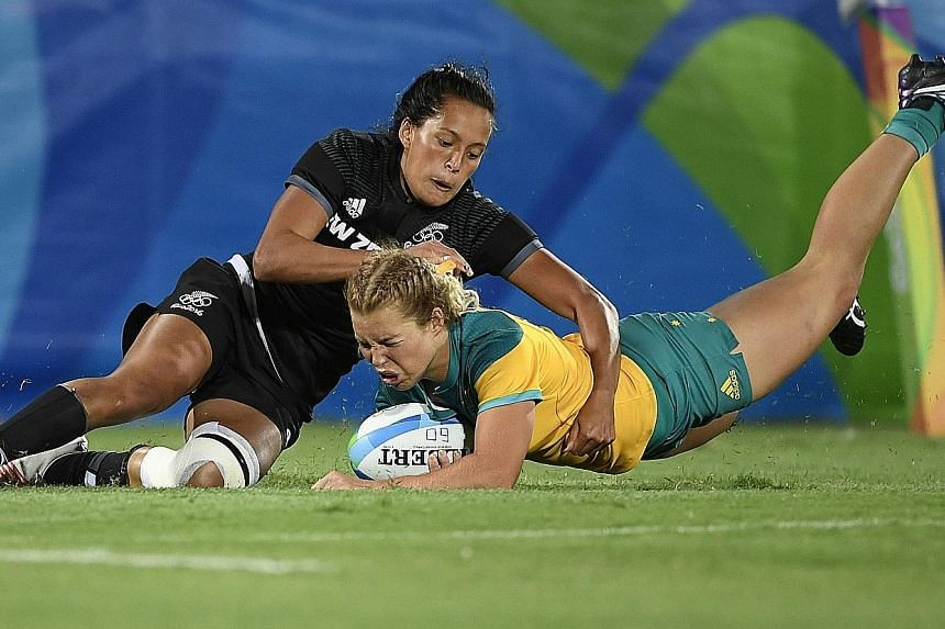 Australia's Emma Tonegato (left) making it 5-5 in the women's rugby sevens final. Two minutes later, New Zealand's Portia Woodman (above) was yellow-carded for a deliberate knock-on and Australia took advantage by going 10-5 up within seconds. They w