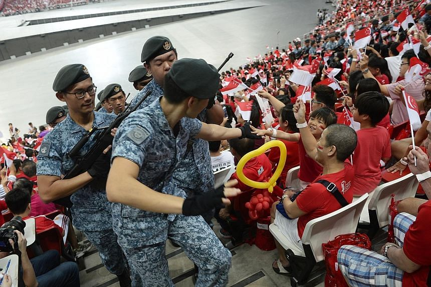 Above: Parade-goers get on their feet and roar as the Kallang Wave sweeps across the National Stadium - the site where the tradition was born. Many whip out the Singapore scarf for the ritual which lasts a good three to four minutes. Left: Participan