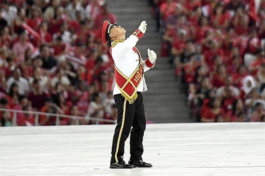 Drum major Chua Keng Hwee tosses his mace during the military tattoo segment. The military expert, who also had to control the tempo of the music played by the combined band, went on to deftly catch the staff.