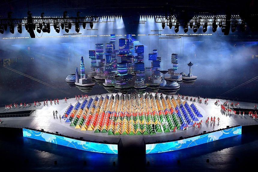 """Rising high above the stage, an imposing """"Sky City"""" prop of iconic landmarks and futuristic buildings projects Singapore's future skyline. The most challenging aerial prop in the show, it took nine months to design and two months to construct. Beneat"""