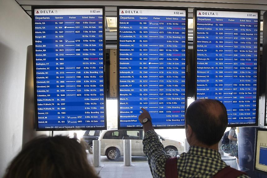 Passengers checking monitors displaying Delta Airlines flight departure schedules at LaGuardia Airport in New York on Monday. Monday morning is one of the busiest times for both airlines and travellers as business travellers begin their work week.