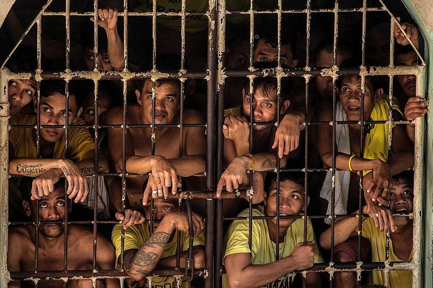 Inmates look out from their cell in Quezon City Jail. Originally built for 800 inmates, the prison now houses almost 4,000. The overcrowded conditions at the prison have prompted the government to build new facilities.
