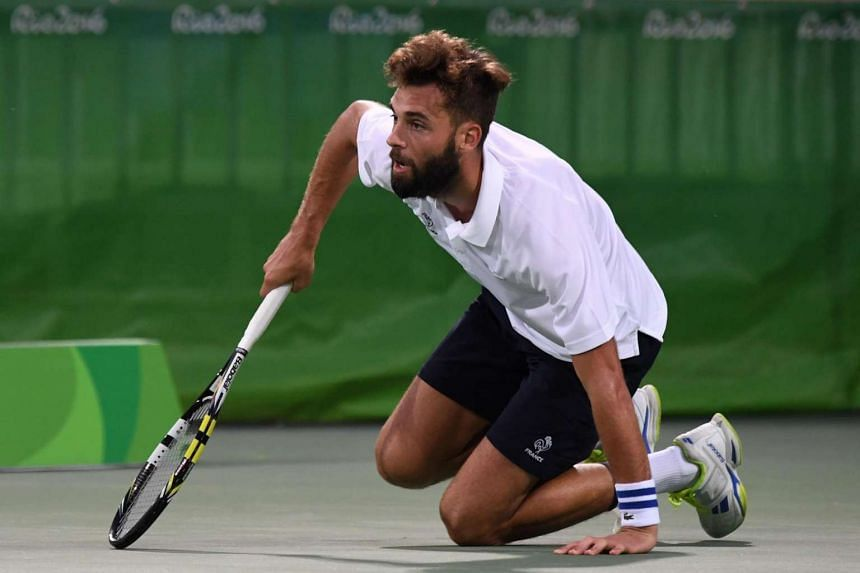 France's Benoit Paire kneels on the court during his men's second round singles tennis match against Italy's Fabio Fognini at the Olympic Tennis Centre of the Rio 2016 Olympic Games in Rio de Janeiro on August 9.