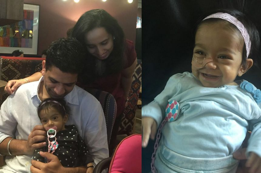 Mr Sandeep Singla with his wife, Ms Neha Wilson, and eight-month-old daughter Zarouhi, who is fighting for her life at the NUH paediatric intensive care unit.