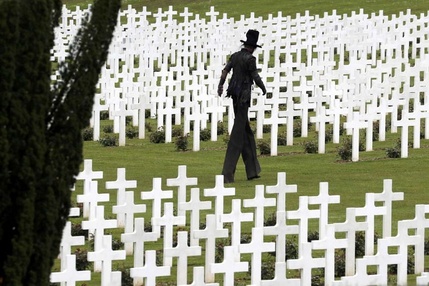 A performer depicts death walks among tombstones at the French National cemetery outside the Douaumont Necropolis and Ossuary.