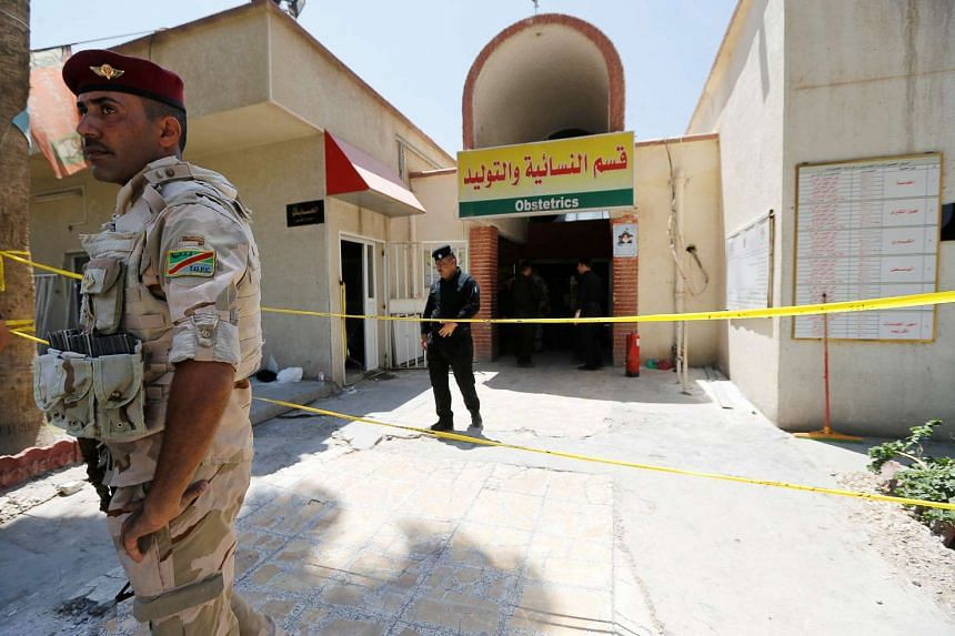 Iraqi security forces stand guard in front of a maternity ward after a fire broke out at Yarmouk hospital in Baghdad, Iraq on Aug 10, 2016.