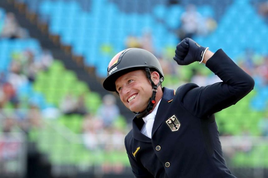 Gold medalist Michael Jung of Germany celebrates after winning the eventing individual jumping competition.