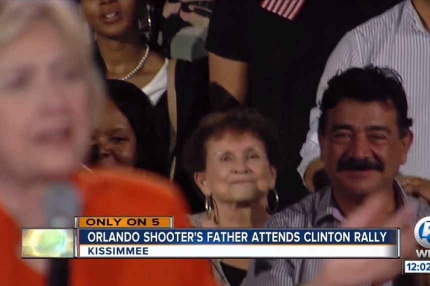 Seddique Mateen (right) sits listening to Hillary Clinton in a screenshot from  US TV news.