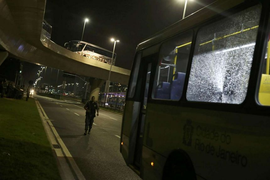 Broken windows on a media bus after they shattered from gunfire while journalists were being transported between Olympic venues.