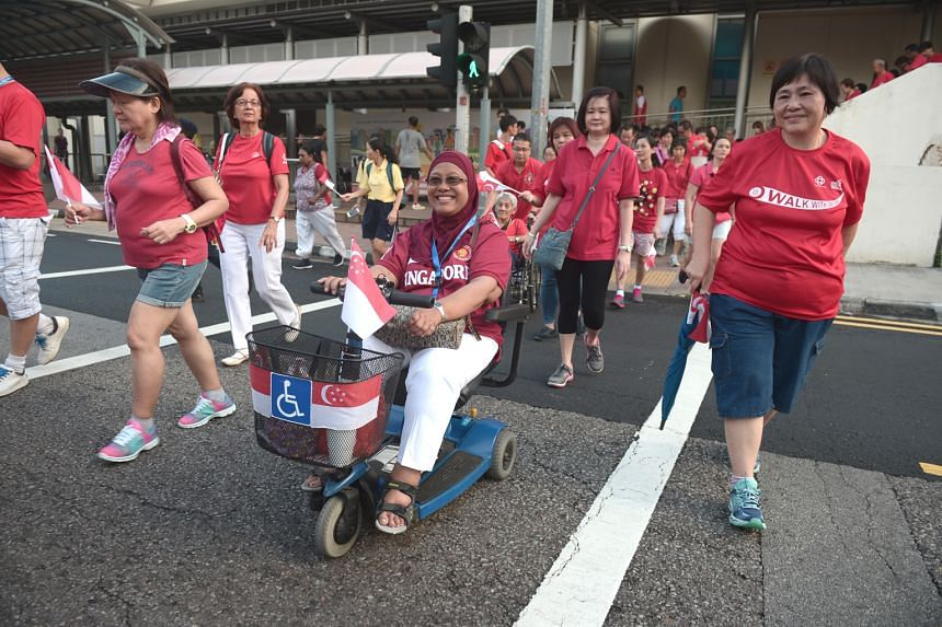 Members of the public and the Hua Yuan association take part in a mass community walk as part of National Day celebrations yesterday.
