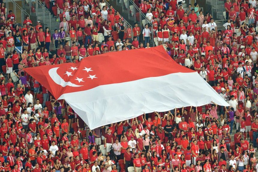 The atmosphere inside the 55,000-seat stadium is electric as members of the audience pass along one of 16 giant Singapore flags during the singing of the National Anthem.