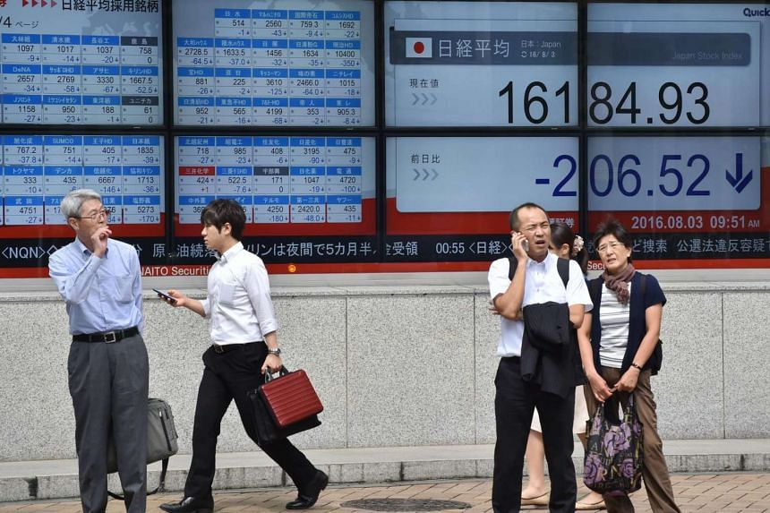 Pedestrians stand in front of an electric quotation board displaying the Nikkei key index of the Tokyo Stock Exchange in Tokyo on August 3.