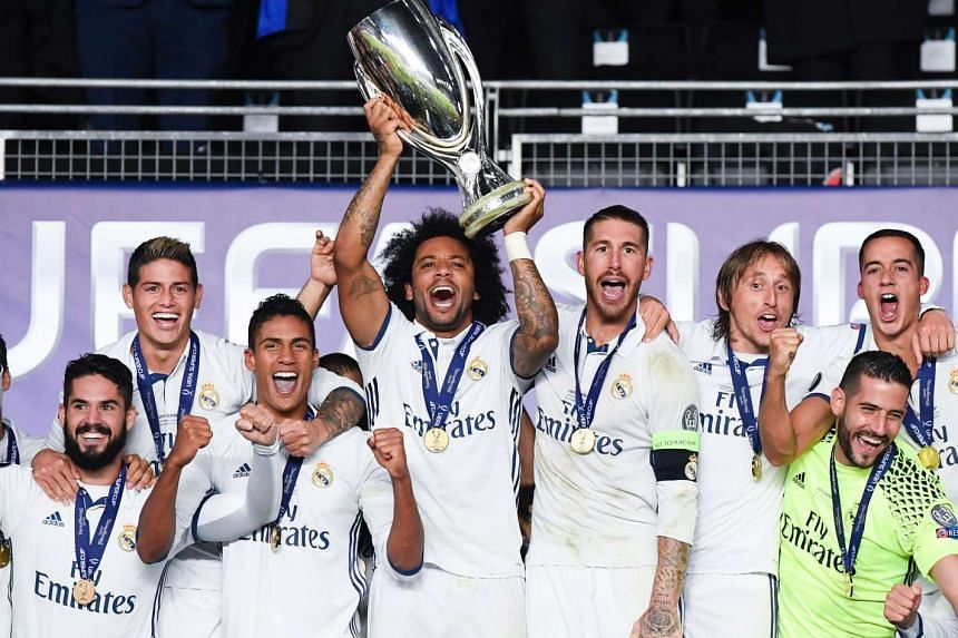Real Madrid's players celebrate with the trophy after winning the UEFA Super Cup final football match.