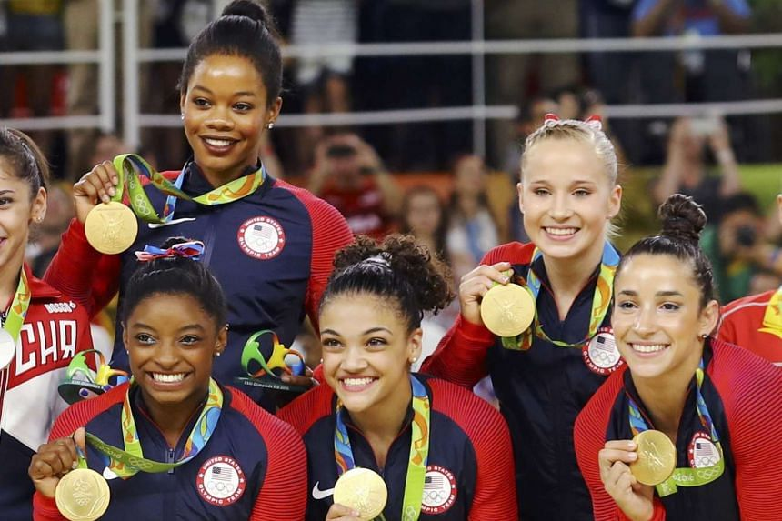 The US team members pose with their gold medals on the podium after winning the women's team final.