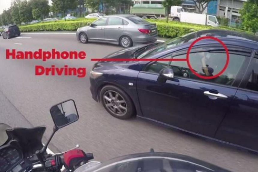 A driver using his mobile phone while driving on the expressway.
