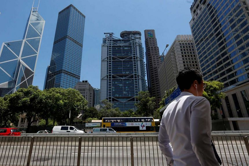 A man walks in front of the financial central district in Hong Kong.